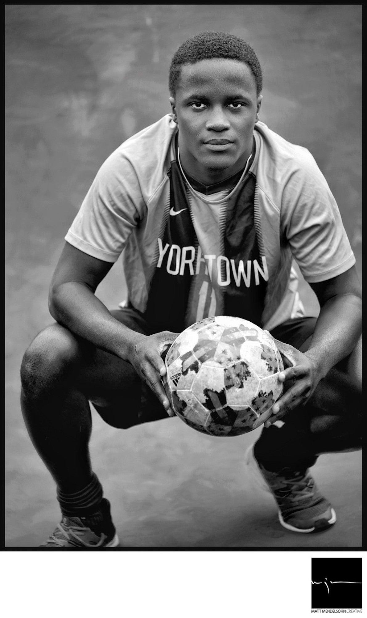 Alpha-Universe-Matt-Mendelsohn-senior-soccer-player-pius-kneeling-holding-soccer-ball.jpeg